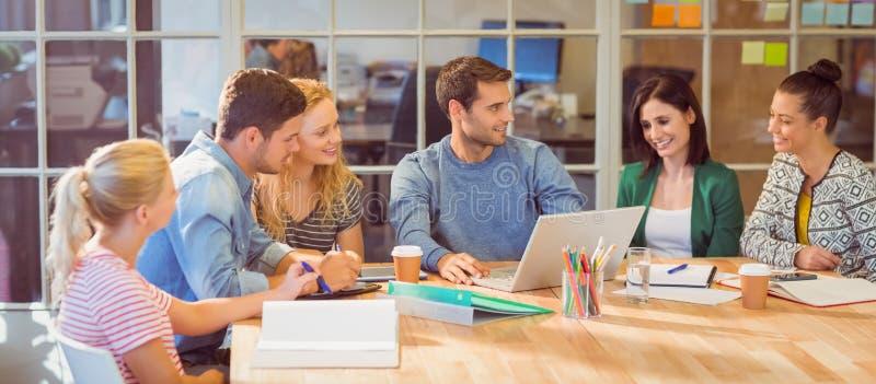 Grupo de colegas jovenes que usan el ordenador portátil imagen de archivo