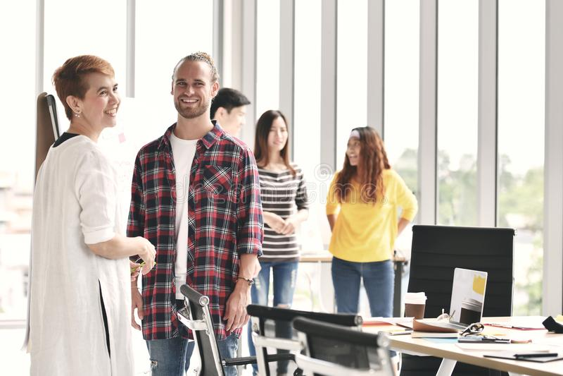 Grupo de colegas que discuten el trabajo en el ajuste casual imagen de archivo