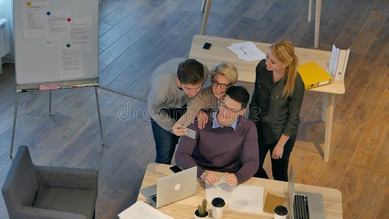 Grupo de colegas que se divierten en su oficina que toma el selfie con smartphone fotografía de archivo