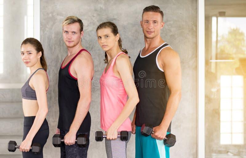 Grupo de colocar motivada gente de la diversidad y de llevar a cabo la pesa de gimnasia, equipo amistoso adolescente joven deport imagen de archivo