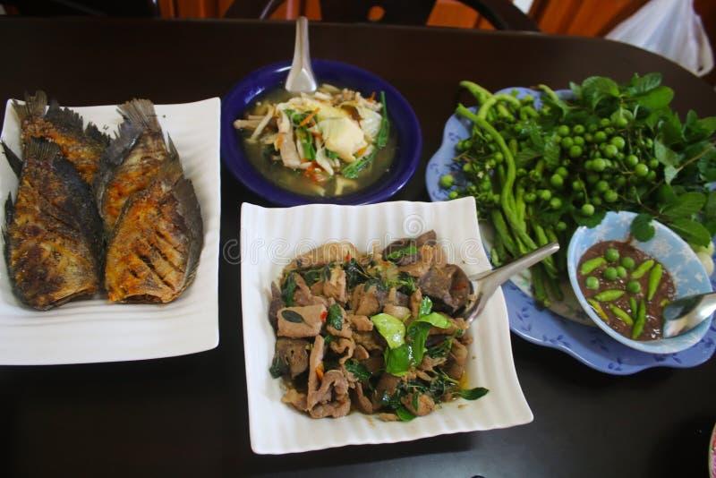 Grupo de comida tailandesa en la tabla, sofrito con cerdo y albahaca, goma del chile con los pescados vegetales, fritos, Sukiyaki fotos de archivo