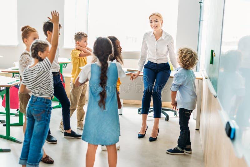 grupo de compañeros de clase que se colocan alrededor de profesor en la sala de clase fotografía de archivo