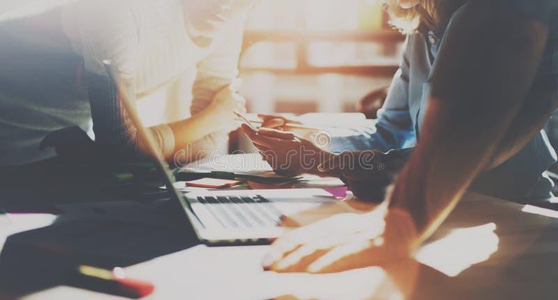 Grupo de compañeros de trabajo jovenes que trabajan junto en la oficina moderna en la puesta del sol Mujer que sostiene smartphon fotos de archivo
