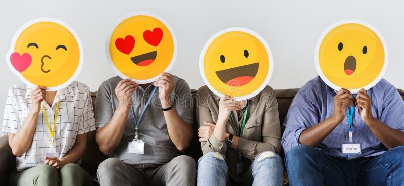 Grupo de compañeros de trabajo que sostienen emoticons foto de archivo