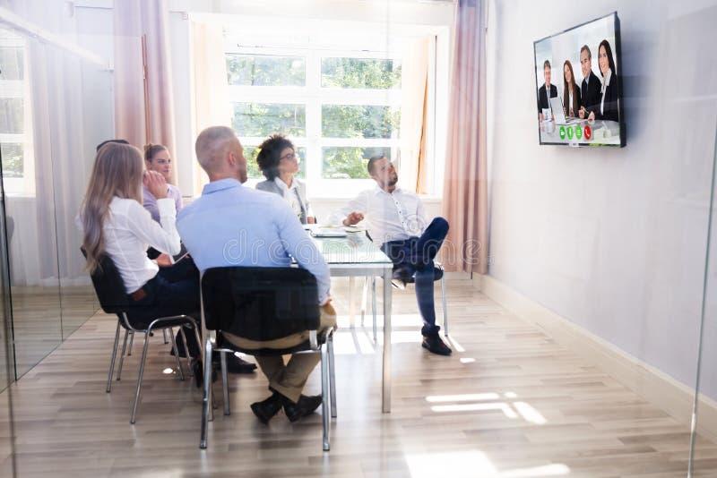 Grupo de comunicación video de los empresarios diversos en la sala de reunión fotos de archivo libres de regalías