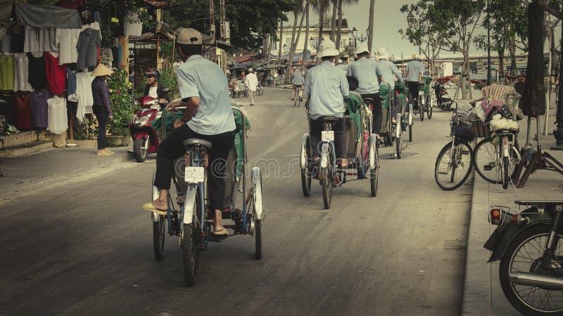 Grupo de conductores ciclos que conducen en la tensión, ciudad antigua Vietnam de Hoi An foto de archivo