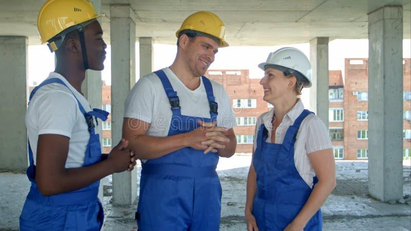 Grupo de constructores sonrientes en cascos de protección que hablan en el emplazamiento de la obra fotografía de archivo libre de regalías