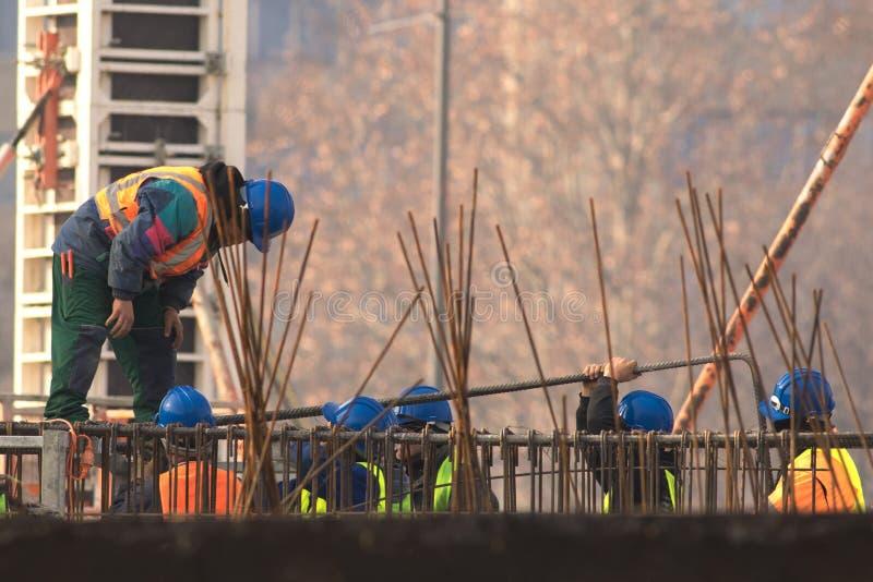 Grupo de construtores com o capacete azul no canteiro de obras foto de stock