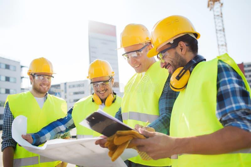 Grupo de construtores com PC e modelo da tabuleta imagens de stock