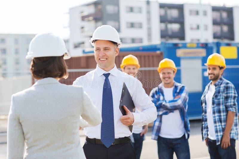 Grupo de construtores de sorriso nos capacete de segurança fora foto de stock royalty free