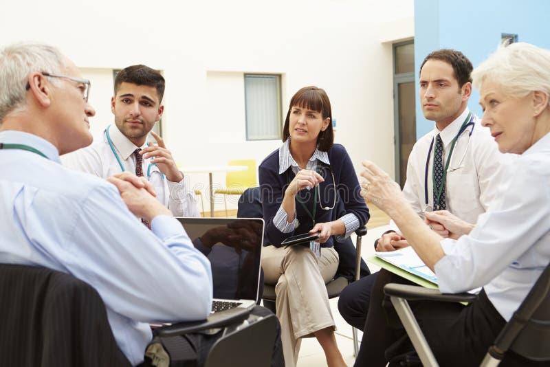 Grupo de consultantes que sentam-se na tabela na reunião do hospital imagem de stock