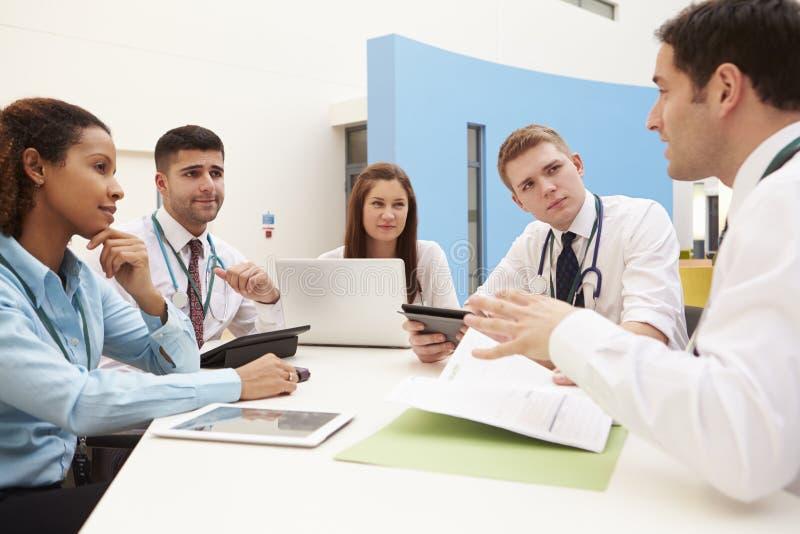 Grupo de consultantes que sentam-se na tabela na reunião do hospital fotos de stock royalty free