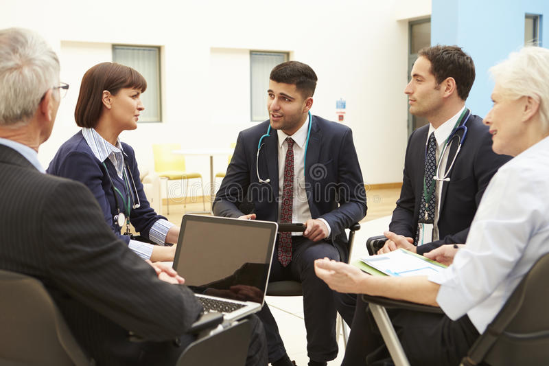 Grupo de consultores que se sientan en la tabla en la reunión del hospital fotografía de archivo