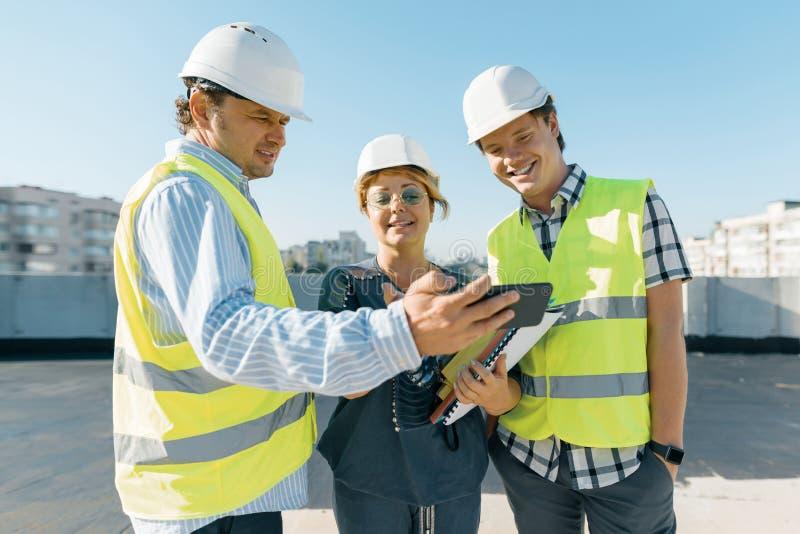 Grupo de coordenadores, construtores, arquitetos no terreno de construção Conceito da construção, do desenvolvimento, dos trabalh fotografia de stock royalty free