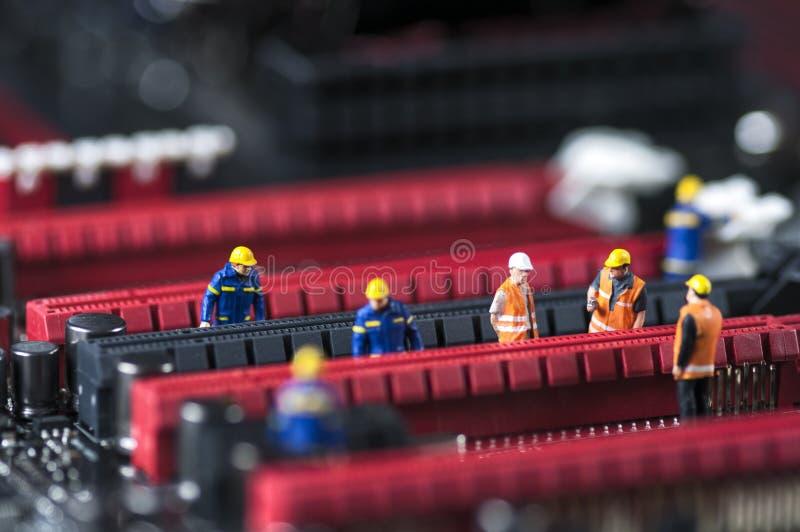 Grupo de coordenadores que fixam a placa de circuito do computador imagem de stock