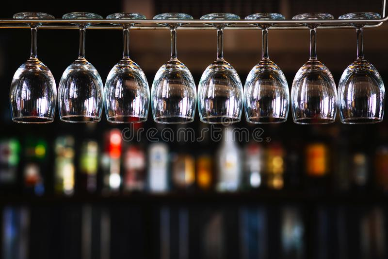 Grupo de copas de vino que cuelgan sobre un estante de la barra en pub y restaura imagen de archivo libre de regalías