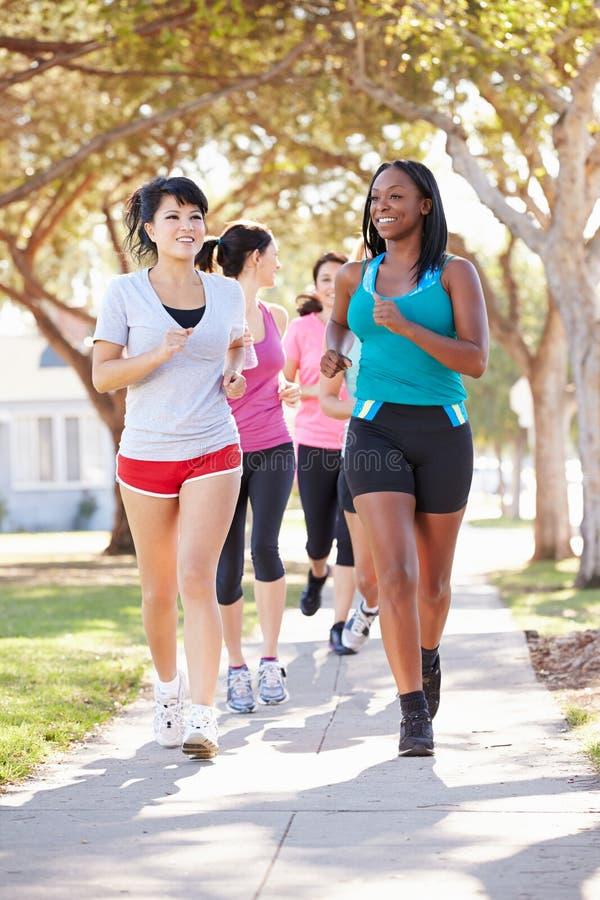 Grupo de corredores fêmeas que exercitam na rua suburbana imagens de stock