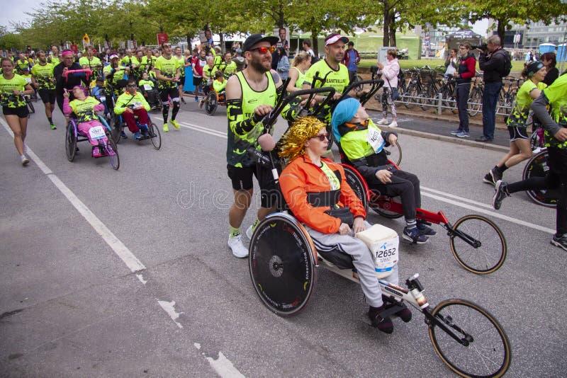 Grupo de corredores de maratón que empujan las sillas de rueda de funcionamiento con las personas discapacitadas que les ayudan p imagenes de archivo