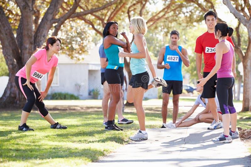 Grupo de corredores que aquecem-se antes da raça imagem de stock royalty free