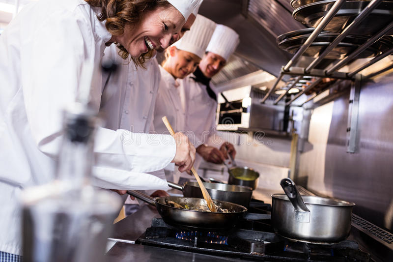 Grupo de cozinheiro chefe que prepara o alimento na cozinha foto de stock royalty free