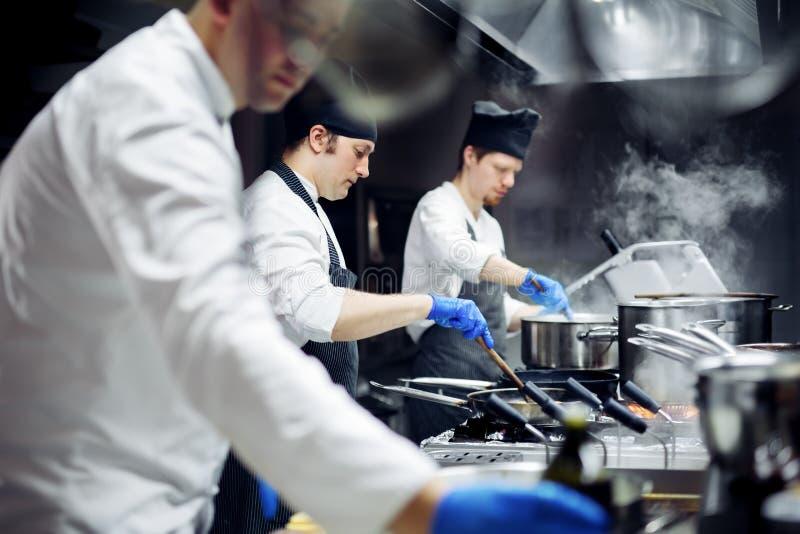Grupo de cozinheiros chefe que trabalham na cozinha imagens de stock