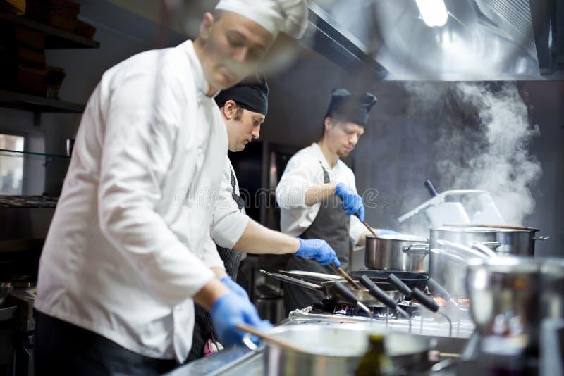 Grupo de cozinheiros chefe que trabalham na cozinha imagem de stock
