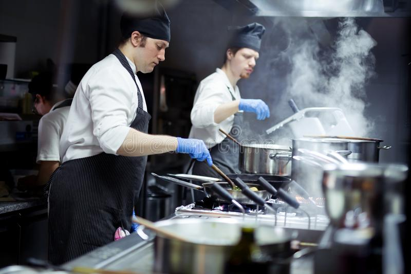 Grupo de cozinheiros chefe que trabalham na cozinha foto de stock royalty free