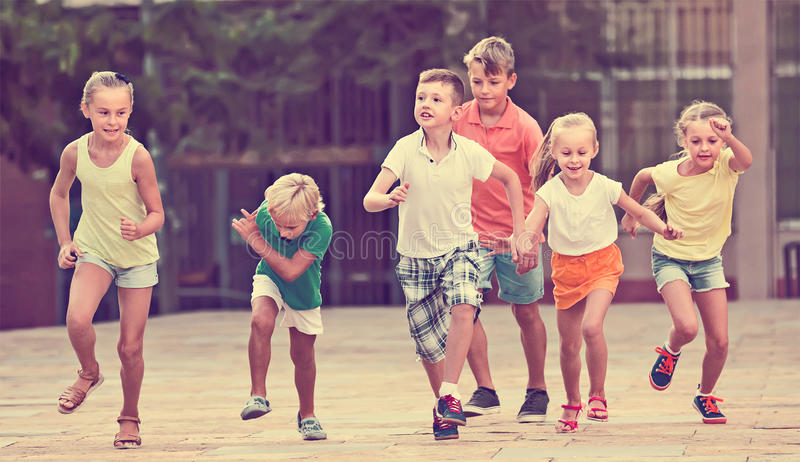 Grupo de crianças amigáveis que correm junto na cidade no verão imagem de stock