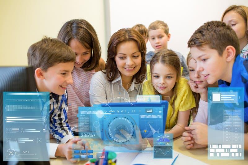 Grupo de crianças com o PC do professor e da tabuleta na escola imagens de stock royalty free