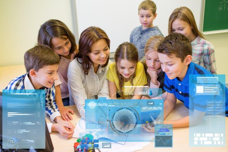 Grupo de crianças com o PC do professor e da tabuleta na escola fotos de stock