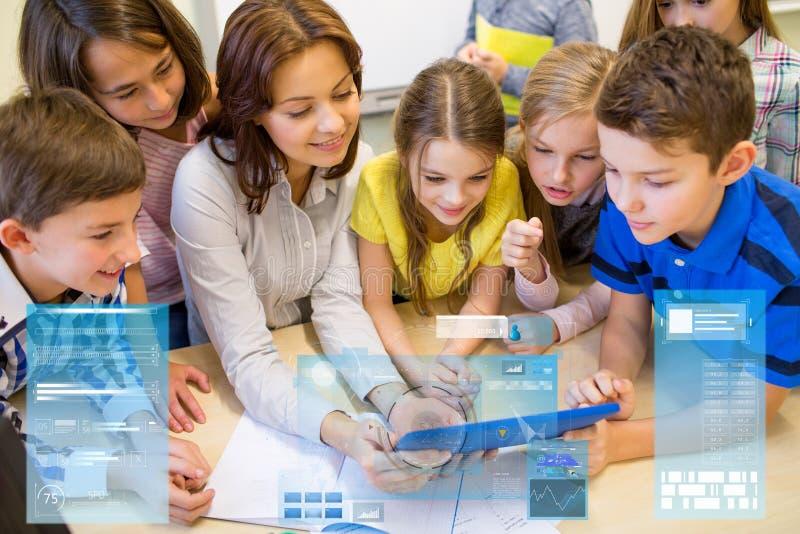 Grupo de crianças com o PC do professor e da tabuleta na escola imagem de stock