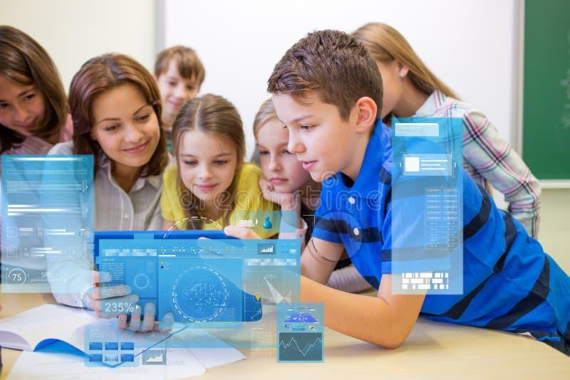 Grupo de crianças com o PC do professor e da tabuleta na escola fotografia de stock royalty free