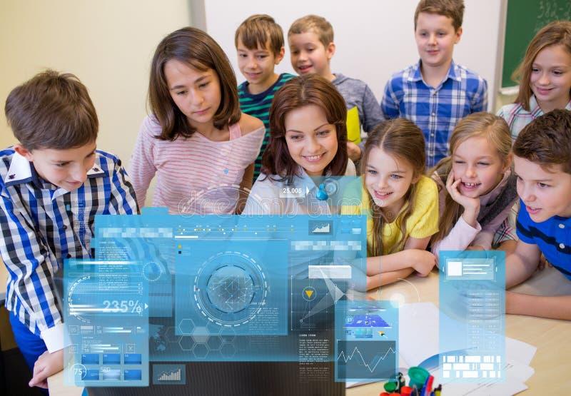 Grupo de crianças com professor e computador na escola foto de stock