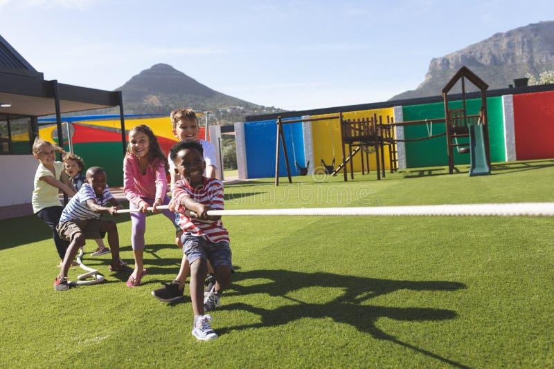 Grupo de crianças da escola que jogam o conflito fotografia de stock royalty free