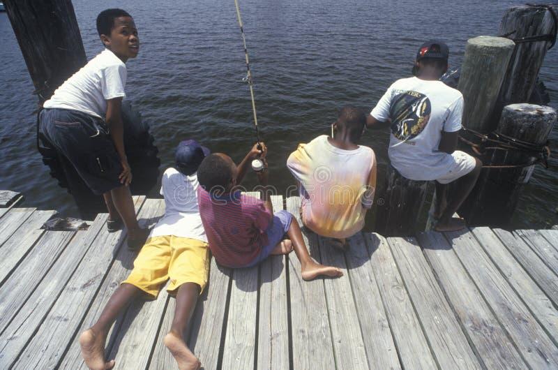 Grupo de crianças do African-American que pescam fora da doca, Ft Myers, FL imagem de stock