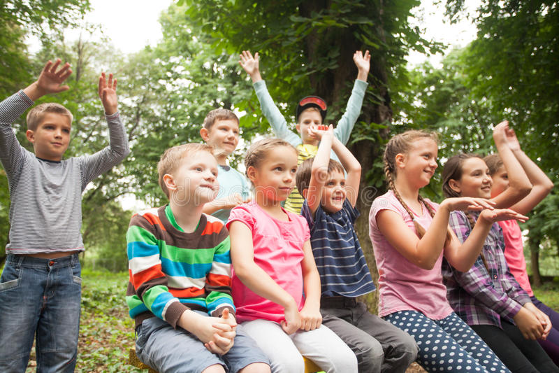 Grupo de crianças em um banco de parque imagens de stock