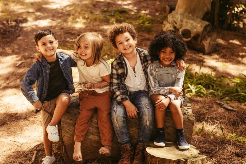 Grupo de crianças em um log de madeira fotografia de stock