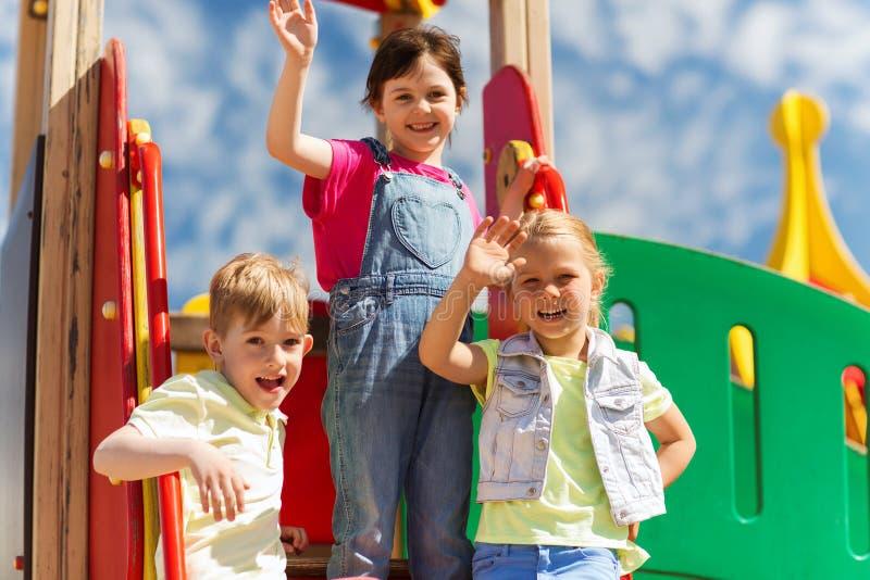 Grupo de crianças felizes que acenam as mãos no campo de jogos fotos de stock