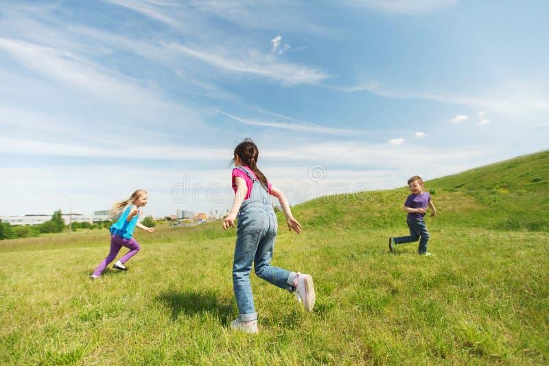 Grupo de crianças felizes que correm fora imagem de stock