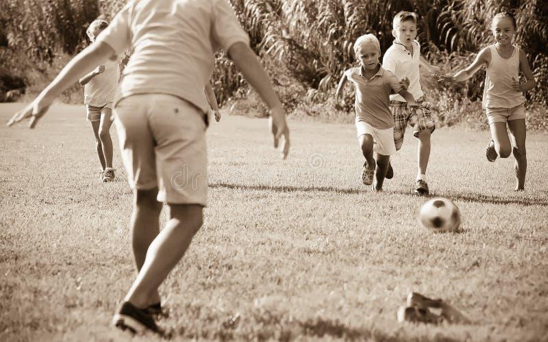 Grupo de crianças felizes que jogam o futebol junto no gramado verde em p fotografia de stock royalty free