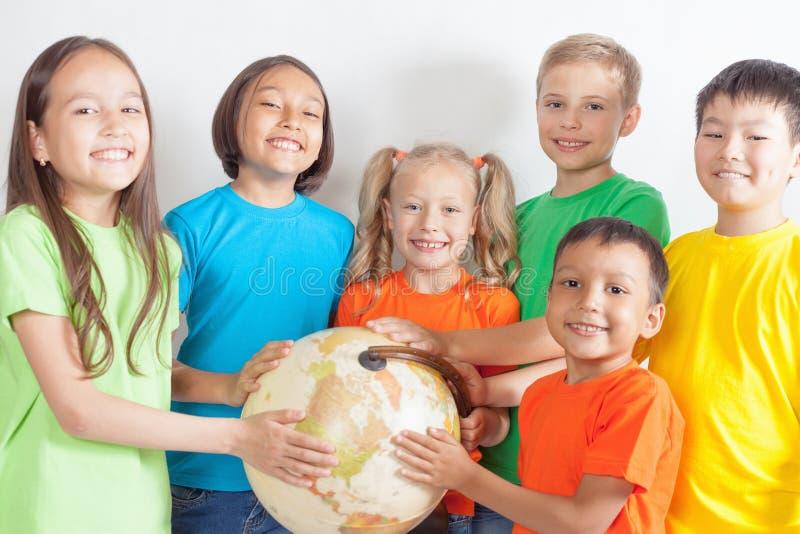 Grupo de crianças internacionais que guardam a terra do globo foto de stock royalty free