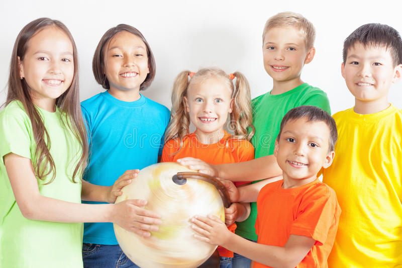 Grupo de crianças internacionais que guardam a terra do globo fotografia de stock royalty free
