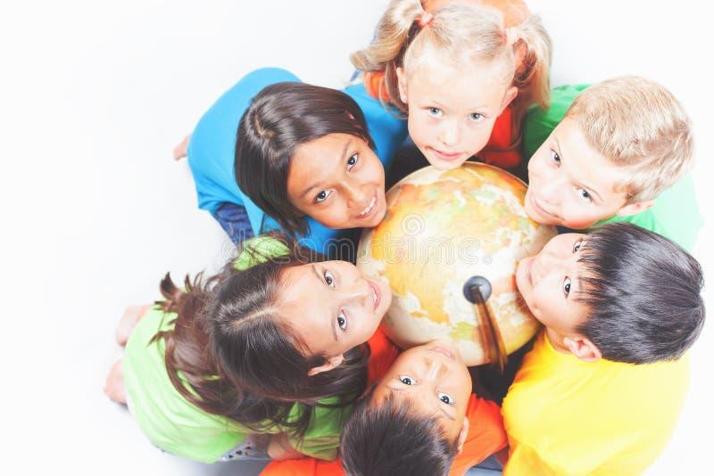 Grupo de crianças internacionais que guardam a terra do globo imagens de stock royalty free