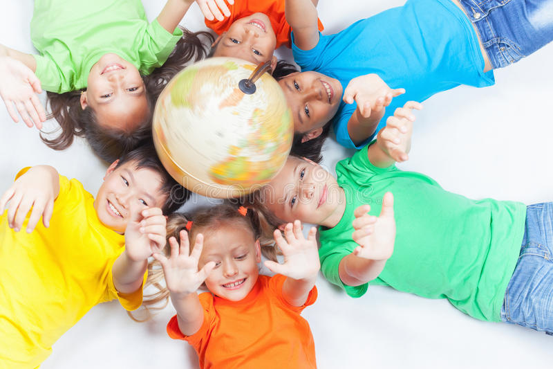 Grupo de crianças internacionais que guardam a terra do globo imagem de stock