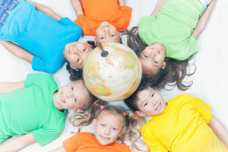 Grupo de crianças internacionais que guardam a terra do globo foto de stock