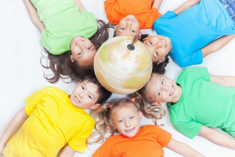 Grupo de crianças internacionais que guardam a terra do globo fotografia de stock
