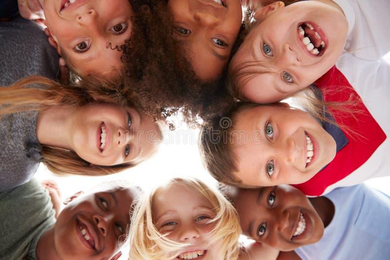 Grupo de crianças multiculturais com os amigos que olham para baixo na câmera fotografia de stock royalty free