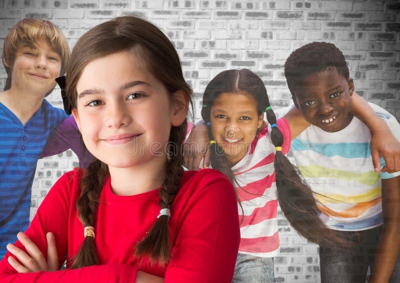Grupo de crianças na frente da parede de tijolo fotos de stock royalty free