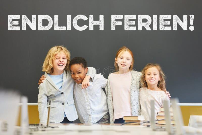 Grupo de crianças na frente do quadro-negro com feriados enfim! slogan imagem de stock royalty free