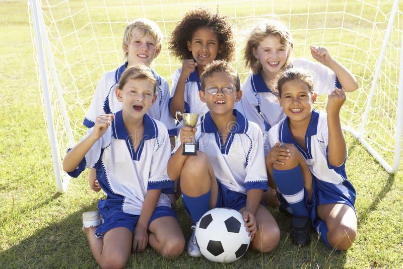 Grupo de crianças no futebol Team Celebrating With Trophy imagens de stock